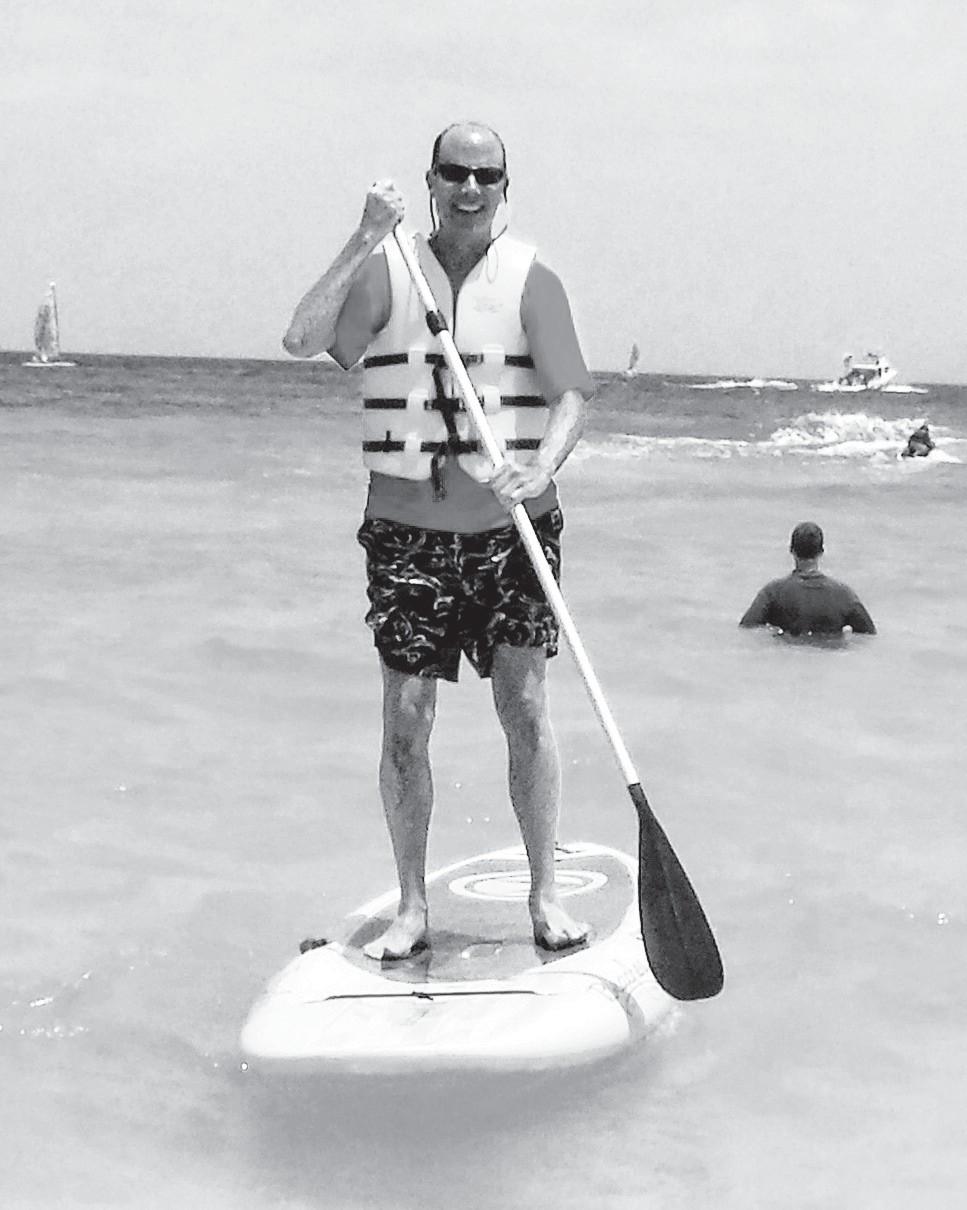 PADDLE BOARDING ANYONE?—Consider learning a new sport on vacation. Here, the author tries his hand at stand-up paddle boarding.