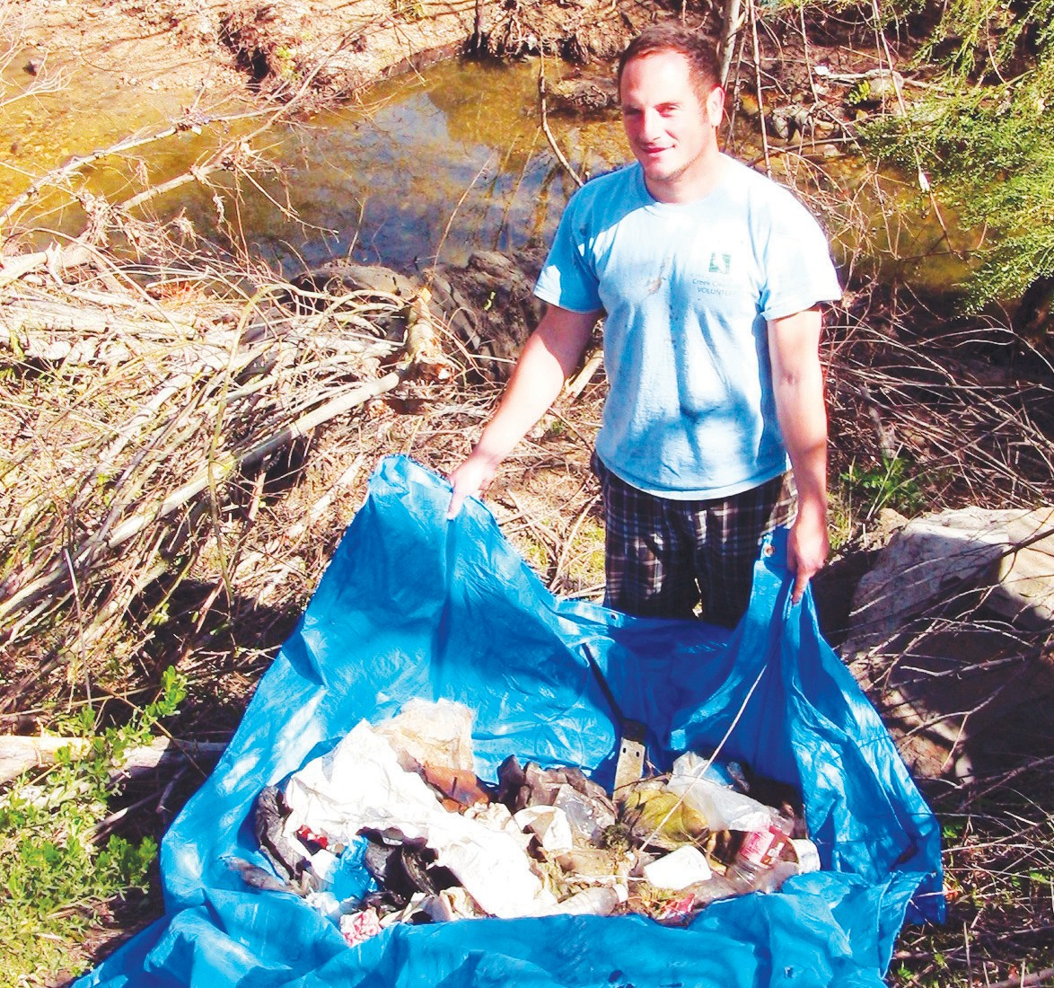 BIG HAUL—A volunteer carries off a load of trash during a previous similar creek cleanup. Last year saw the removal of about 2,000 pounds of garbage. ACORN FILE PHOTO