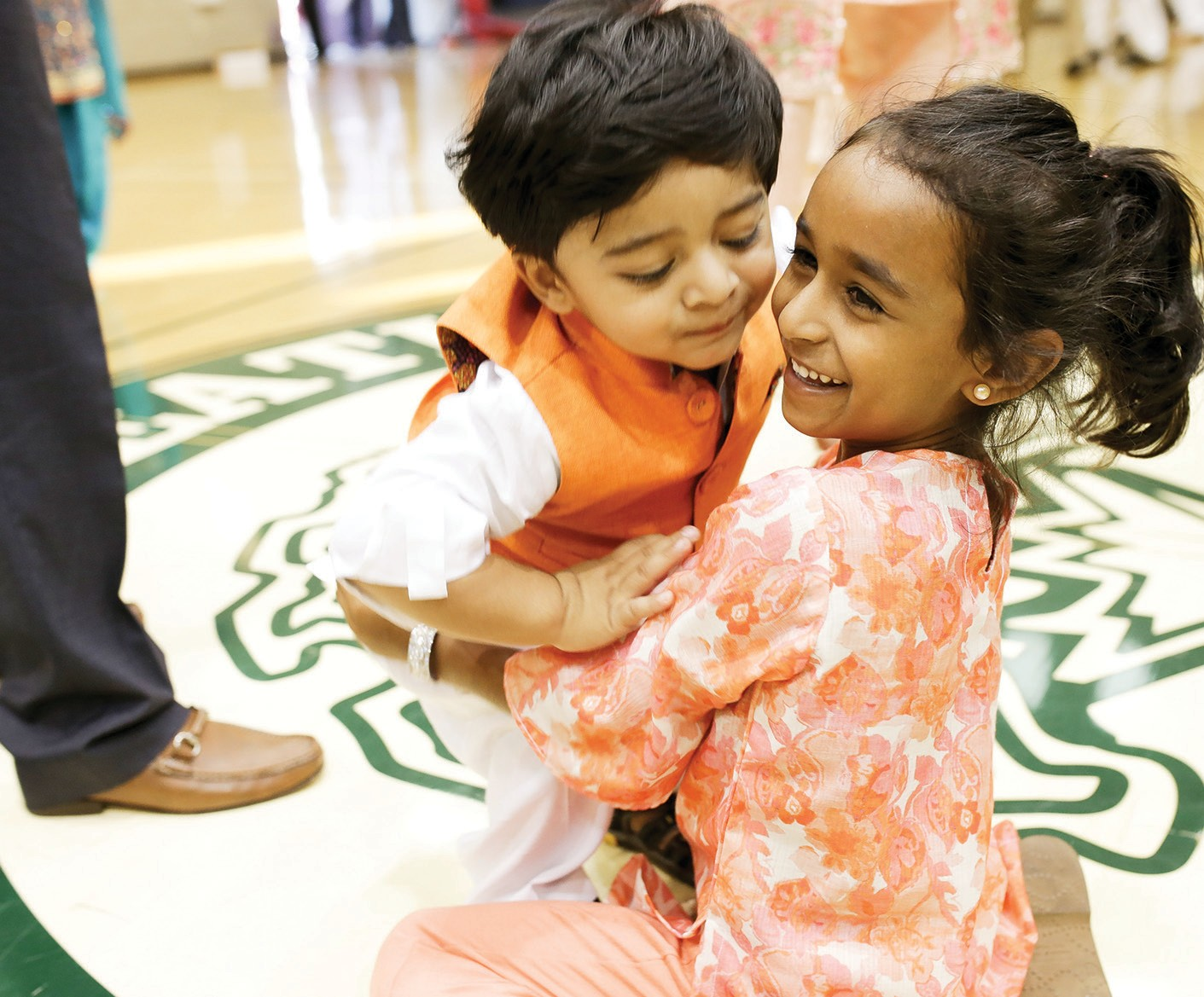 A HAPPY TIME—Six-year-old Zara Konkader, right, embraces 1-year-old Shaan Iqbal, both of Newbury Park, following an Eid-al-Adha prayer on Sept. 1 at Dos Venitos Community Center in Newbury Park. BOBBY CURTIS/Acorn Newspapers