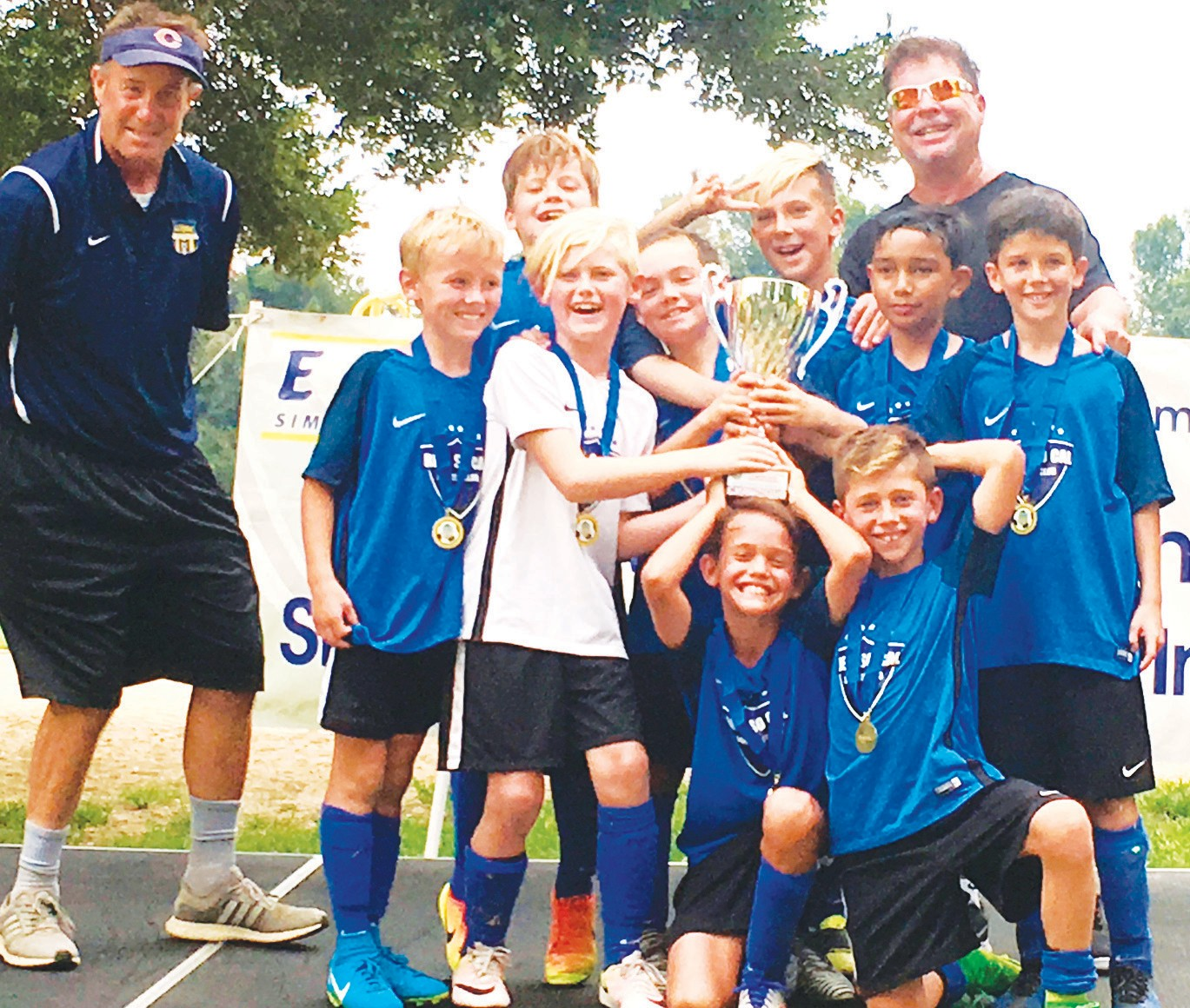 A REAL SWEET WIN—Real SoCal North Ranch boy's U-10 soccer team winsfirst place in the 2017 Simi Valley Labor Day Invitational Tournament at 9-2. Celebrating the victory with medals and trophy are director of coaching Mike Evans, Liam Lambert, Jerry Shifman, Justice Sullivan, Braeden Wynalda, Kaleb Nehdar, coach Kenny Dapello, Santiago Diaz, Todd Norton, Daniel Geft and Ren Thomas.