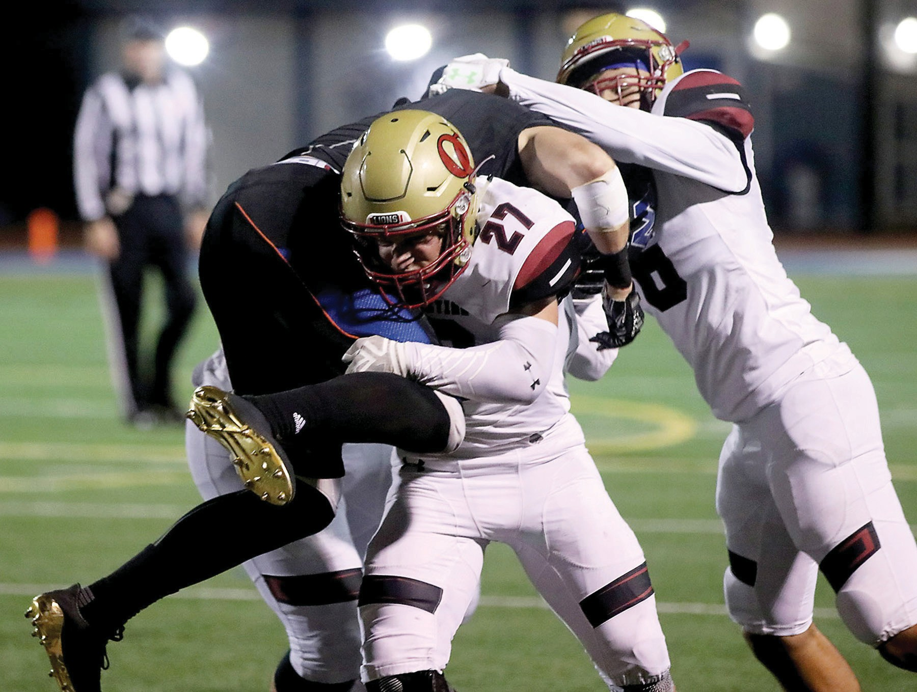 HITCHIN' A RIDE—Oaks Christian High football safety Nate Lenthall, No. 27, tackles Westlake's Nathan Brooks during the Lions' 42-7 road win Nov. 3. Photos by ROB VARELA/Acorn Newspapers