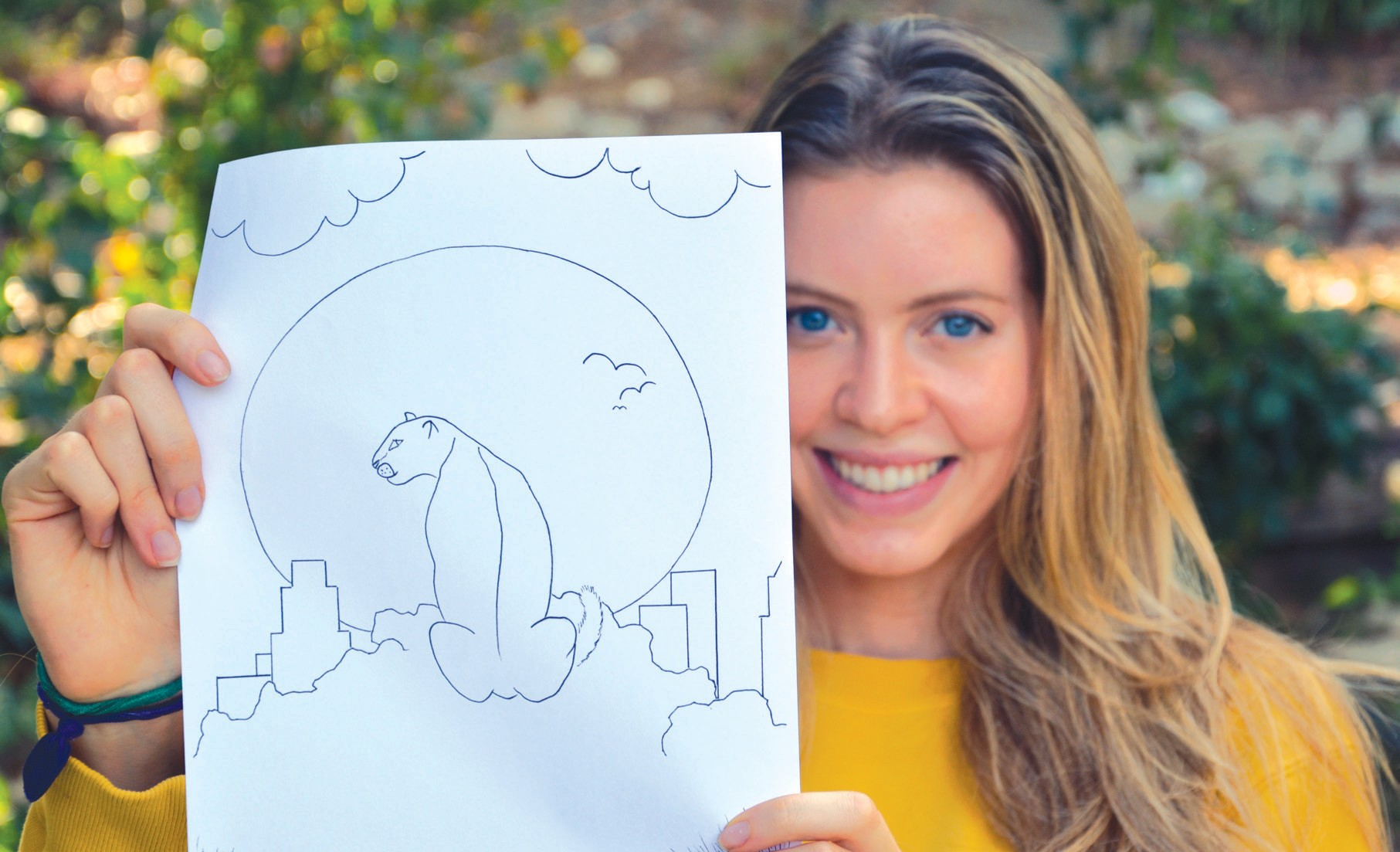 """PURRFECT PUMA—Olivia Lester, above, a student at Agoura High School, is one of the contributing artists in a coloring and activity book about the life of Griffith Park's resident mountain lion, P-22. Titled """"We Heart P-22,"""" below, the book about the famous puma has inspired many artists and writers. Courtesy photo"""