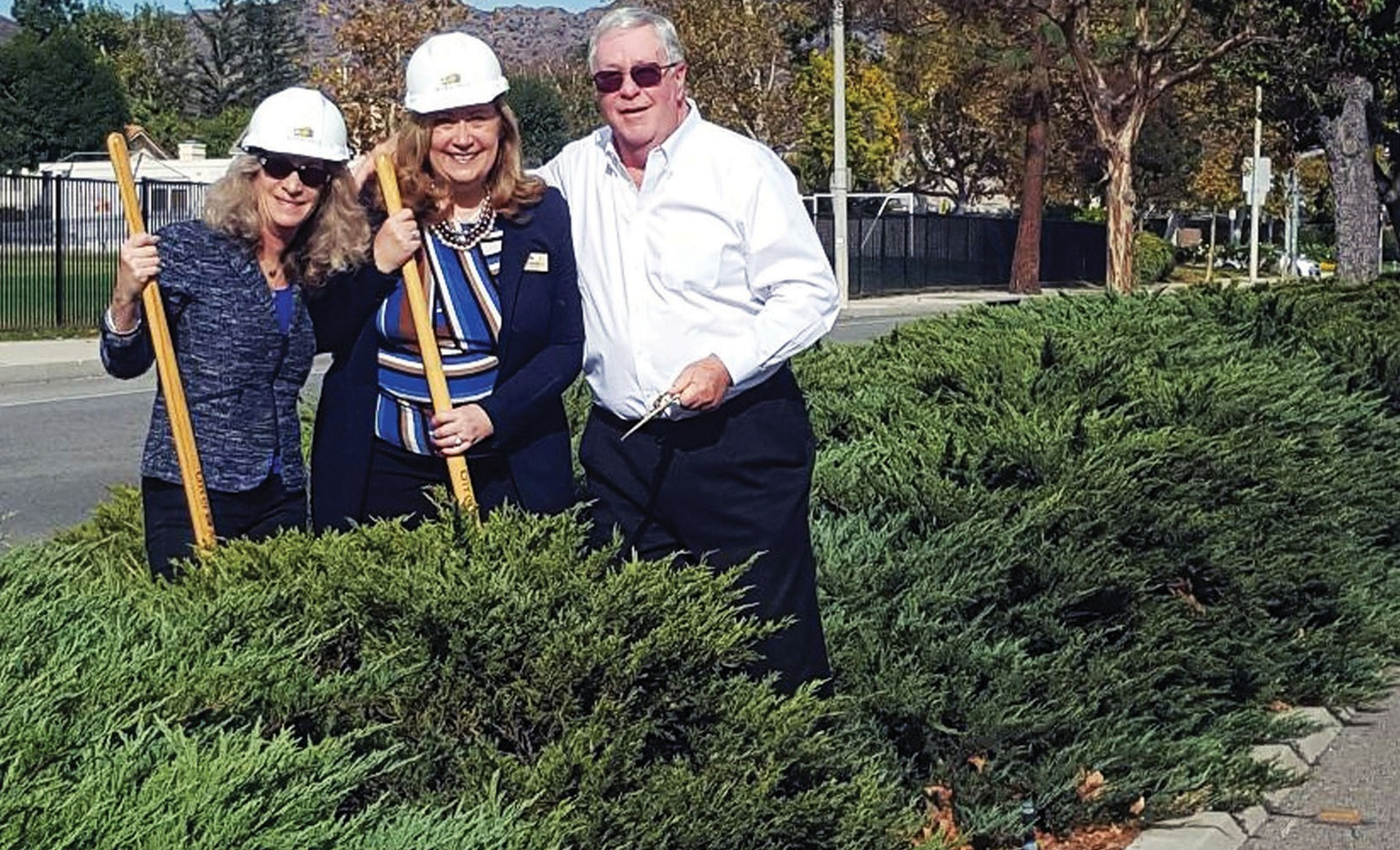 GOODBYE JUNIPERS—From left, Agoura Hills City Councilmembers Illece Buckley Weber, Linda Northrup and Denis Weber take thefirst crack at replacing old trees and shrubs along Kanan Road. STEPHANIE BERTHOLDO/ Acorn Newspapers