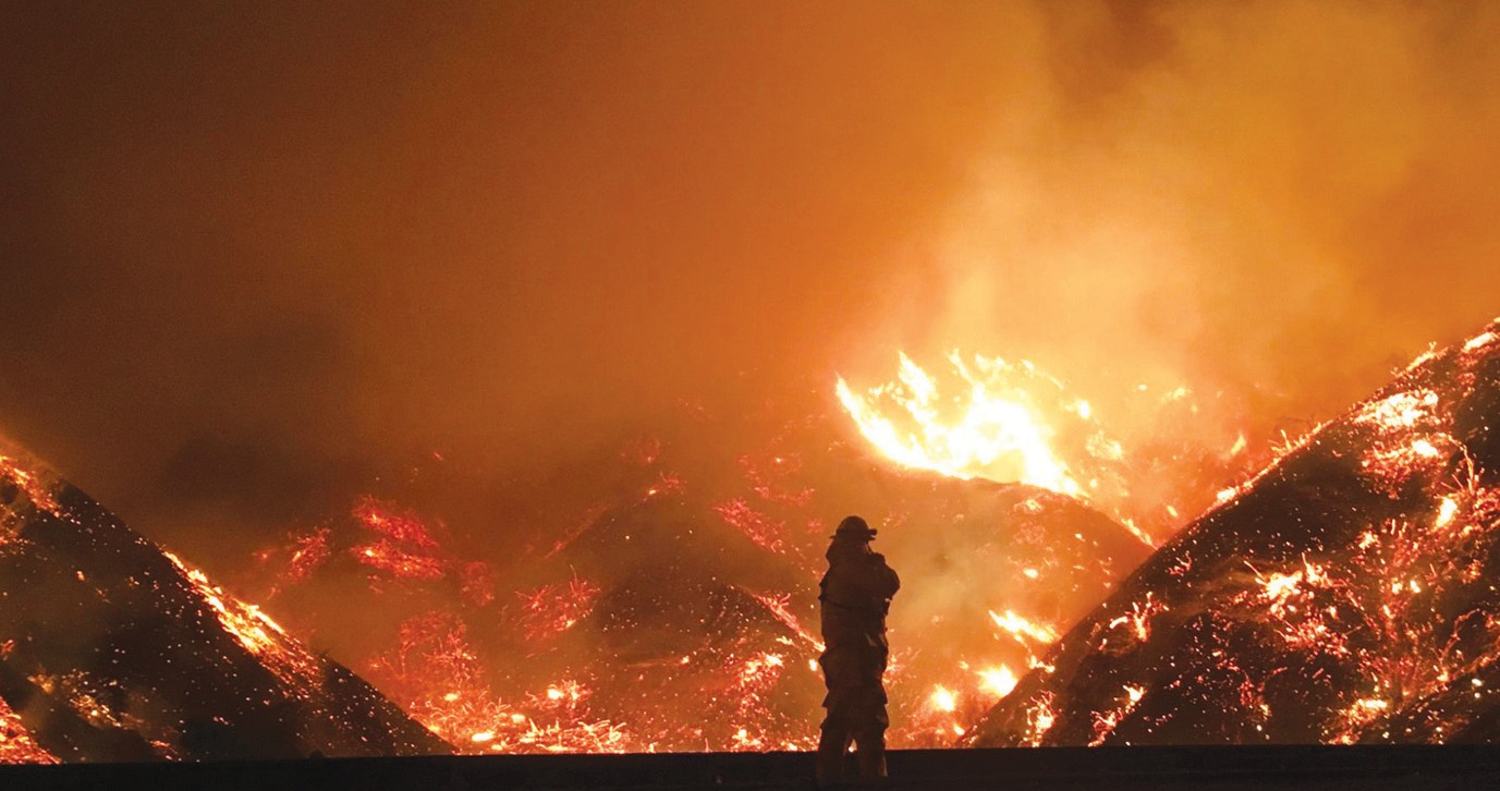 FIRE ON THE MOUNTAIN—Wallace observes the La Tuna Fire in Los Angeles County last summer. Courtesy of Chris Eakman
