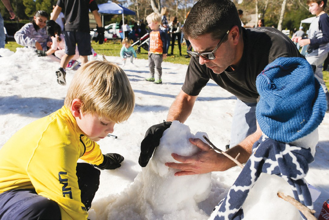 B-R-R-AVING THE C-C-COLD— Above, Richard Burress of Westlake Village and his 6-yearold son, Dayne, build a snowman together during the eighth annual Coats for Casa Pacifica benefit event Jan. 13. The charity coat drive and festivities took place at Three Springs Park in Westlake Village. At left, 4-year-old Jan Sanson of Agoura Hills sleds down a hill of snow. Lydia Gable of Keller Williams Westlake Village and Rick Winters of Winters Financial Group co-hosted the activity.