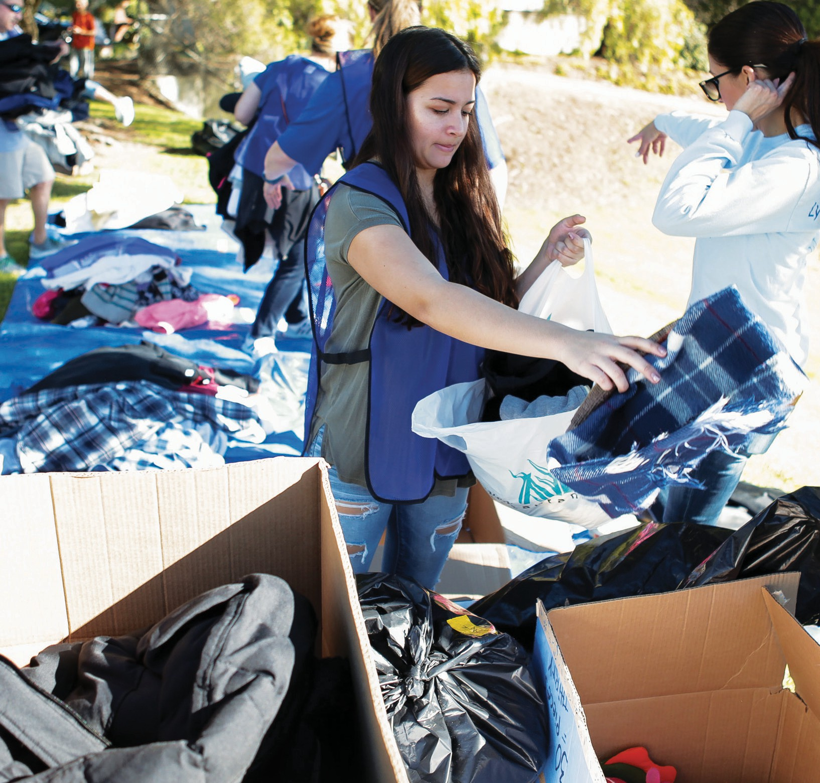 HELPING HANDS—Madi McMichael of Thousand Oaks sorts the donated items during the Coats for Casa Pacifica drive. In addition to playing in the snow, people of all ages took part in arts and crafts and drank free coffee and smoothies while they dropped off their gently used warm clothing items. The annual event benefits Casa Pacifica in Camarillo, an organization that offers free services and shelter to at-risk youth and their families.