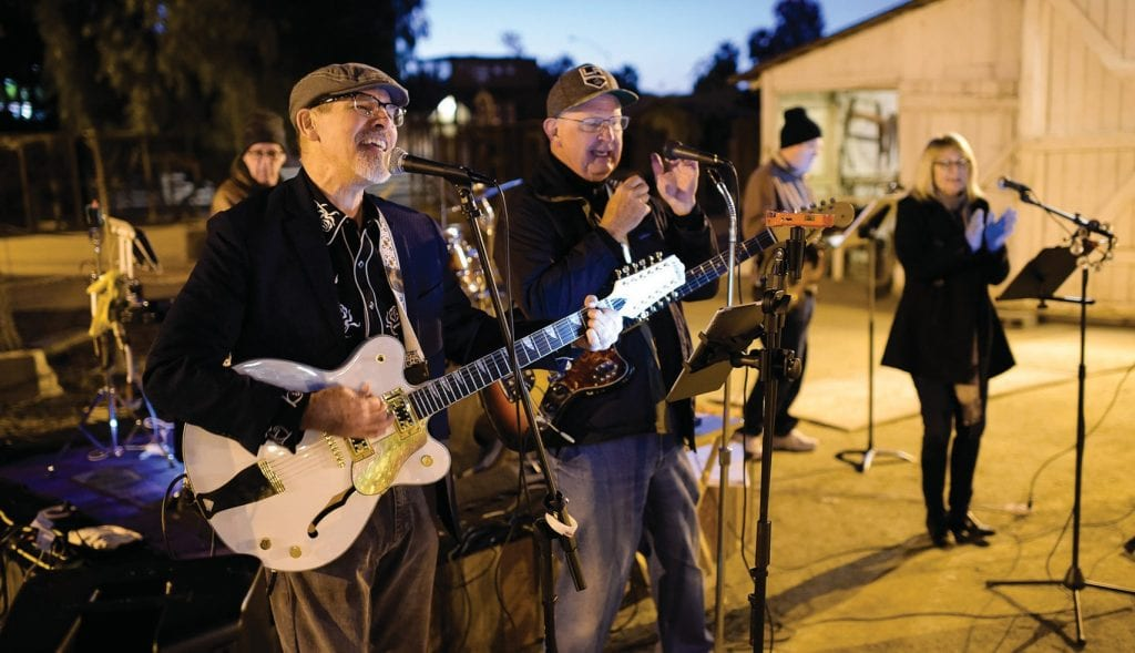 EQUINE CARE—Above, Barney Landgraf, left, and Larry Matz perform with the band Bootleg 8-Tracks during the Night of the Horse fundraiser Feb. 22 at the Leonis Adobe in Calabasas. Right, guests browse the silent auction items at the benefit that will help the California Coastal Horse Rescue organization. Photos by MICHAEL COONS/Acorn Newspapers