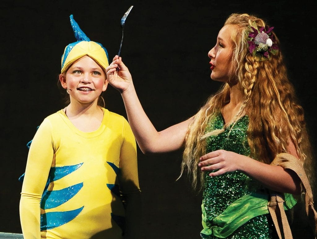 """WATERY TALE— Above, Flounder ( Fiona Fiebig), left, encounters Ariel (Savannah La Verdi) during Lindero Canyon Middle School's production of """"Disney's The Little Mermaid"""" on Mar. 2 at the Agoura High School performing art center. Right, Garrett Khatchaturian plays King Triton in the musical. Photos by BOBBY CURTISAcorn Newspaper"""