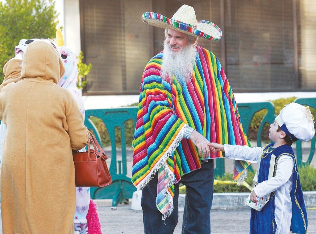 A JOYFUL TIME—Above, Rabbi Moshe Bryski, center, visits with his grandson, Meir Kahanov of Agoura Hills, during Chabad of the Conejo's Mexican-style Purim Festival on March 1. Attendees were encouraged to dress in Mexican clothes. At right, Laurie Street helps her 5-year-old granddaughter Hannah Kryger of Agoura Hills with her hat. Purim is the annual holiday marking a time in ancient Persia when the Jewish people overturned a royal edict designed to wipe them out. The event is recalled in the Book of Esther. Photos by RICHARD GILLARD/Acorn Newspapers