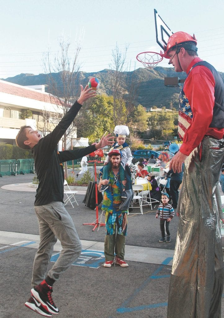 JUMP SHOT—Nathan Kryger, 13 of Agoura Hills, takes aim at the basketball hat of 10-foot-tall Obediah during the Purim festival with Chabad of the Conejo.