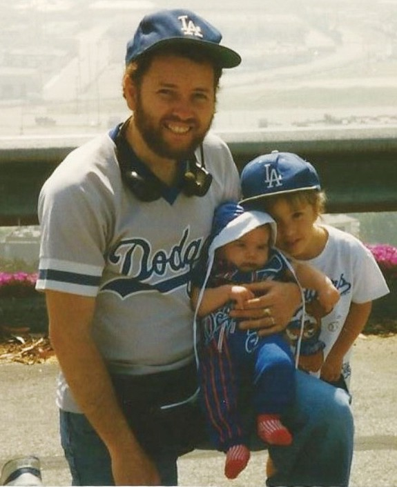 FAMILY TIES—Bob Neher holds his 2-month-old daughter, Felicity, in the Dodger Stadium parking lot on April 8, 1996, Felicity'sfirst home opener. Felicity's sister Samantha is on the right. Courtesy of Cheryl Neher