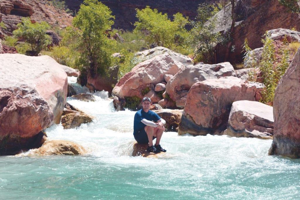 A COOL DUDE—National park traveler Mikah Meyer takes a side hike and cools off in Havasu Creek while rafting on the Colorado River. His journey is a tribute to his father, who died when Meyer was 19. Courtesy of Mikah Meyer