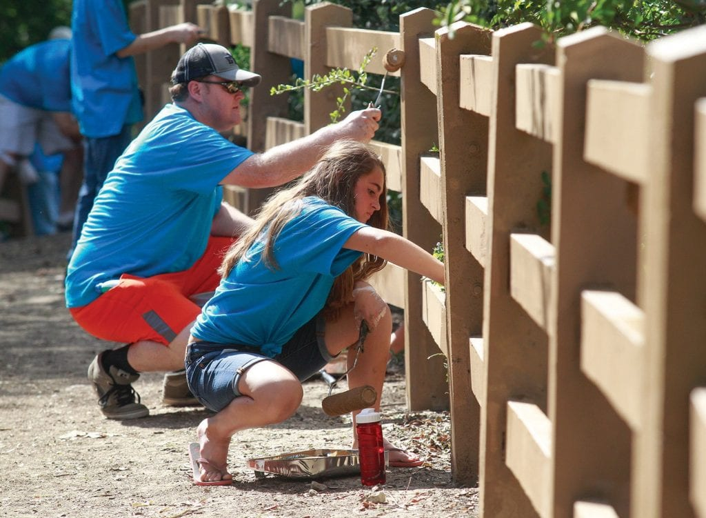 THE BRUSH OFF—Left, 12-year-old Hailey and her father, Phil Thompson, both of Agoura Hills, paint a fence at Old Agoura Park during Community Service Day.