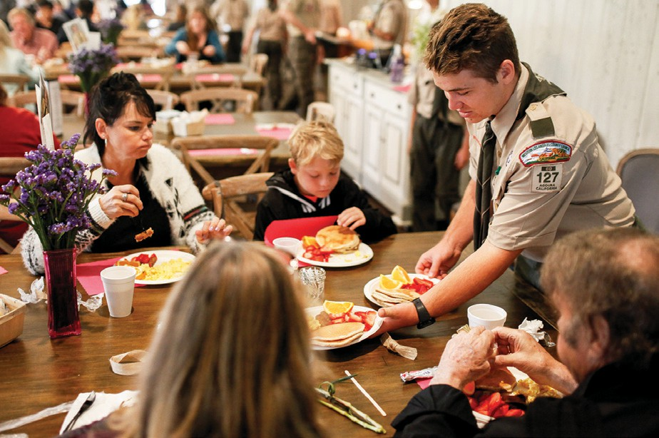 AT YOUR SERVICE—Ali Sarman, 14, of Boy Scout Troop 127 delivers pancakes to the breakfast guests on Mother's Day. The longstanding event honors all local moms.