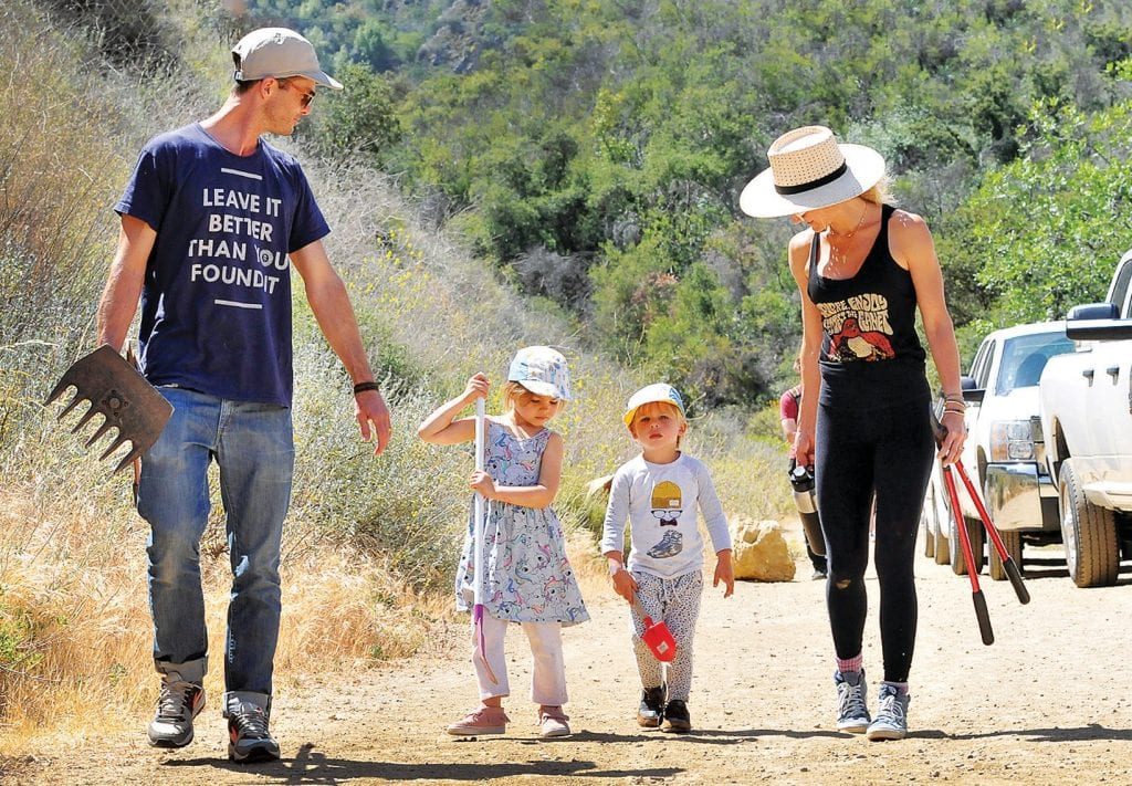 CALLING ALL AGES—Above from left, Parks Project co-founder Keith Eshelman brings his kids 5-year-old Everly and 3-year-old Leo Eshelman to help clear brush from Lookout Trail above Century Lake during National Trails Day on June 2 at Malibu Creek State Park. With them is Kelly Furano. At the annual event , park officials lead volunteer crews on trail cleanup duty to improve the path system.