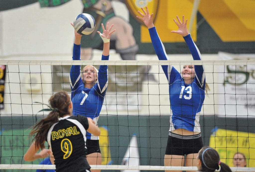 SUCH GREAT HEIGHTS—Meg Graham, right, elevates for a block with Agoura High's girls' volleyball team in a match against Royal in 2012. Graham played four years of Division I volleyball for UC Riverside, starting for three seasons at middle blocker. She'll graduate later this month with a sociology degree. MICHAEL COONS/Acorn Newspapers