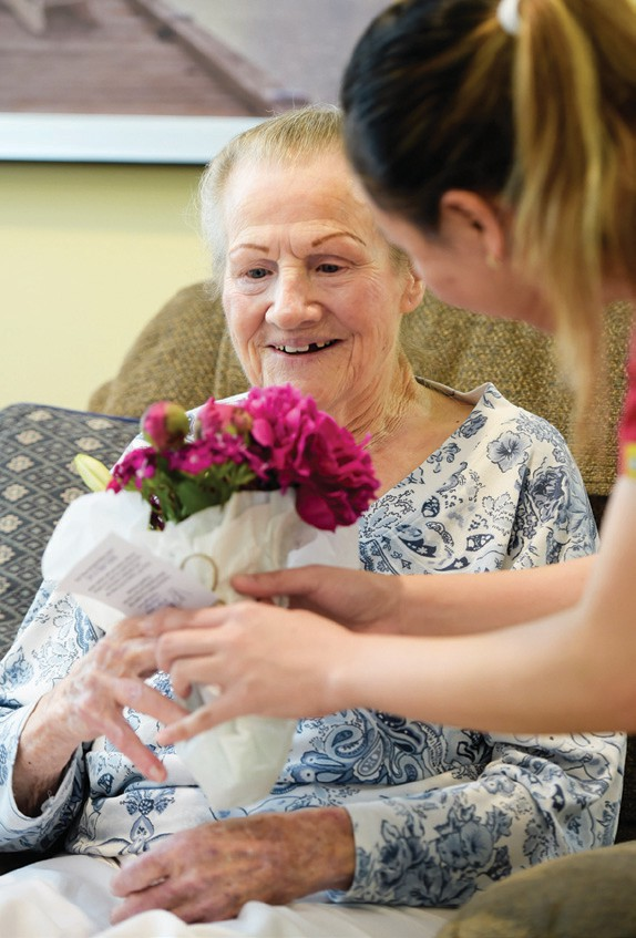 PETAL POWER—Betty Irwin, left, receives a bouquet that brightens her day from Compassionate Care employee Analyn Bernardo. MICHAEL COONS/Acorn Newspapers