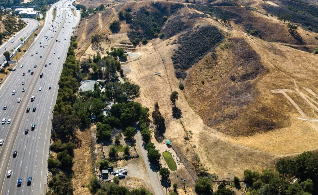 CONSTRUCTION HERE—An aerial view with arrow shows the designated housing site at the end of Canwood Drive just west of Lost Hills Road in Calabasas. The freeway points up toward Agoura Hills. PATRICK GARRETT/Acorn Newspapers