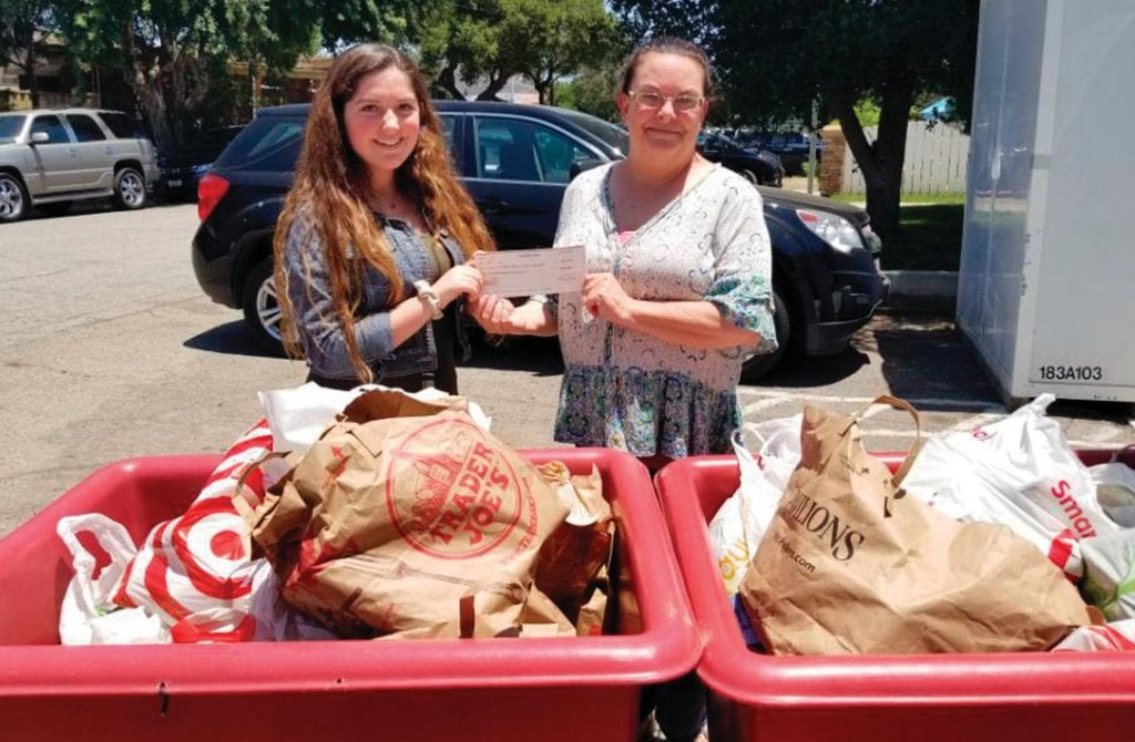 FOOD FOR THOUGHT—Gabriella Senderov, president of Cans4Food at Oak Park High School, gives a donation of 1,400 cans of food and $600 to Jennifer Schwabauer of Manna food bank. Courtesy photo