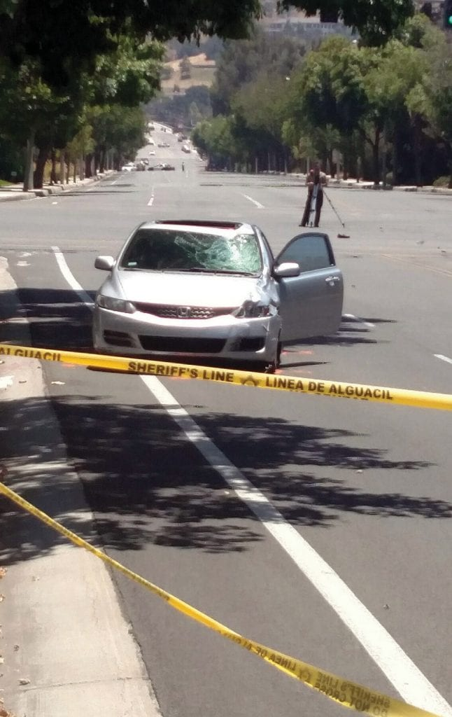 HAPPENED HERE—A traffic investigator examines the scene at T.O. Boulevard and Reyes Adobe Road in Agoura Hills where a man's car collided with a motorized bicycle. The bike rider died. IAN BRADLEY/Acorn Newspapers
