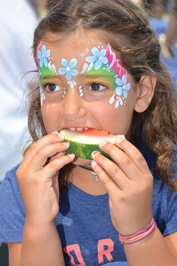 GOOD FOOD—Above, Newbury Park resident Selma Zhiri, 7, munches on a watermelon slice at the Family of Abraham picnic. Below, Sana R. Hassan of Newbury Park cuts the cake. Photos by SUSAN WEININGERAcorn Newspapers