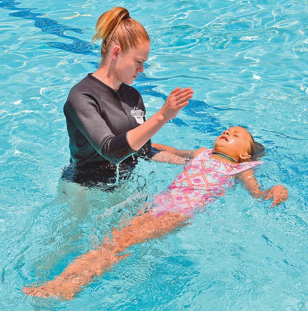 POOL BASICS— Right, young Calabasas swimmer Ellia Alyesh learns how to float on her back with the help of swim instructor Melissa Garb during the July 8 class at The Oaks. Calabasas Mayor Pro Tem David Shapiro and resident Melanie Prince helped organize the event. Far right, swim instructor Jared Weston speaks to the class. For more information about summer water safety, visit PoolSafely.gov. Photos by SUSAN WEININGERAcorn Newspapers