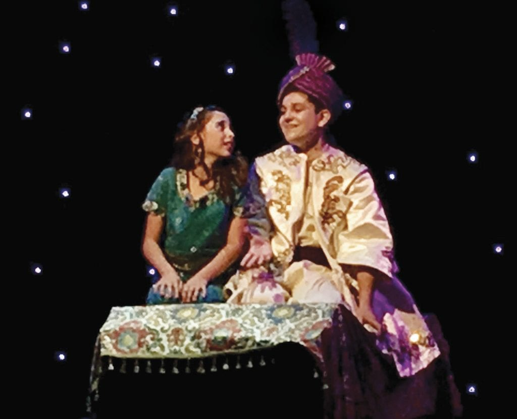 """SOARING HIGH—Princess Jasmine (Mika Silander) and Aladdin (Jack Levi) sing """"A Whole New World"""" aboard their magic carpet. CARY GINELL/Acorn Newspapers"""