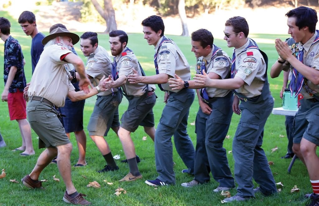 FLYING HIGH-FIVES—Boy Scout Troop 127 Scoutmaster Geoffrey Gunn runs the gauntlet of current and former Eagle Scouts during the troop's annual Alumni Reunion and Court of Honor held July 23 at Chumash Park in Agoura Hills. Gunn, who began his scoutmaster tenure in 1996, has mentored 85 of the 100 Eagle Scouts produced by Troop 127, which began its service in 1946. DIANNE AVERY/Acorn Newspapers