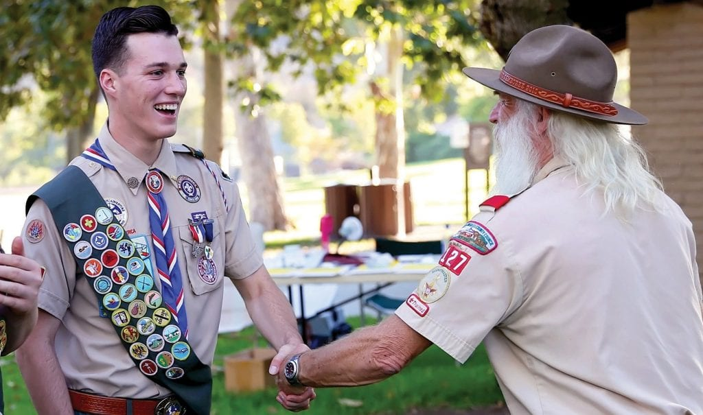 WELL DONE!—Scoutmaster Geoffrey Gunn congratulates 17-year-old Garrett Klinge of Oak Park for becoming Troop 127's 100th Eagle Scout, the highest rank in Boy Scouting. DIANNE AVERY/Acorn Newspapers