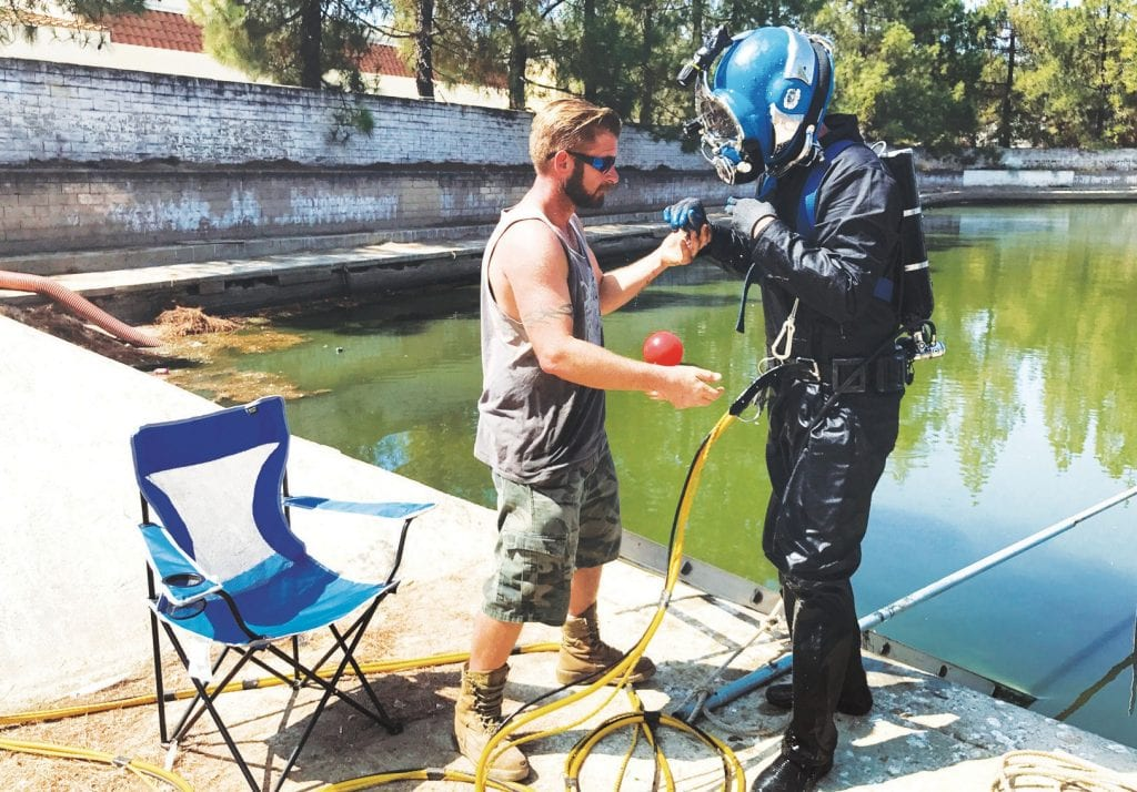 DEEP TROUBLE—A diver and his assistant, standing atop Lake Lindero dam in 2017, prepare for work. A dispute over repairs to the dam led homeowners to demand that the HOA manager, Golf Projects Lindero, be terminated. GPL says it has a valid contract allowing it to stay. Acornfile photo