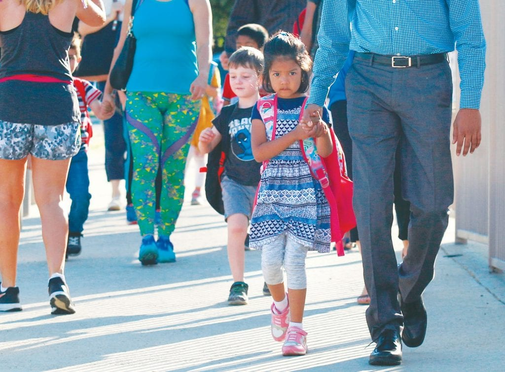 YOUNG MINDS—Kindergartner Navya Matada, 4, stays close to Dad as father and daughter walk onto the campus of Oak Park Elementary School this week. Officials say starting the year earlier and ending thefirst semester before winter break helps student performance. RICHARD GILLARD/Acorn Newspapers