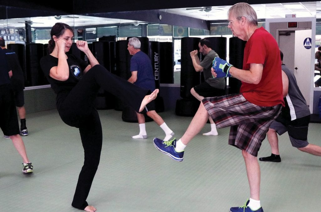 HEALING TOUCH— At right, Jennifer Parkinson, left works with Chris Allen of Agoura Hills during a Neuroboxing class Aug. 13 at Agoura Fitness in Agoura Hills. Bottom right, Westlake resident Jerry Ratzan, 92, spars during a class designed for people with Parkinson's disease. Photos by ROB VARELAAcorn Newspapers