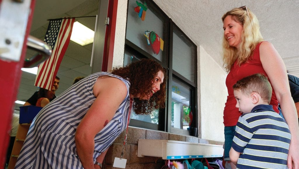 WELCOME, YOUNG MAN!—Amy Licht, kindergarten teacher at Willow Elementary School in Agoura Hills, greets 5-year-old James Birmingham and his mother on thefirst day of school yesterday. RICHARD GILLARD/Acorn Newspapers