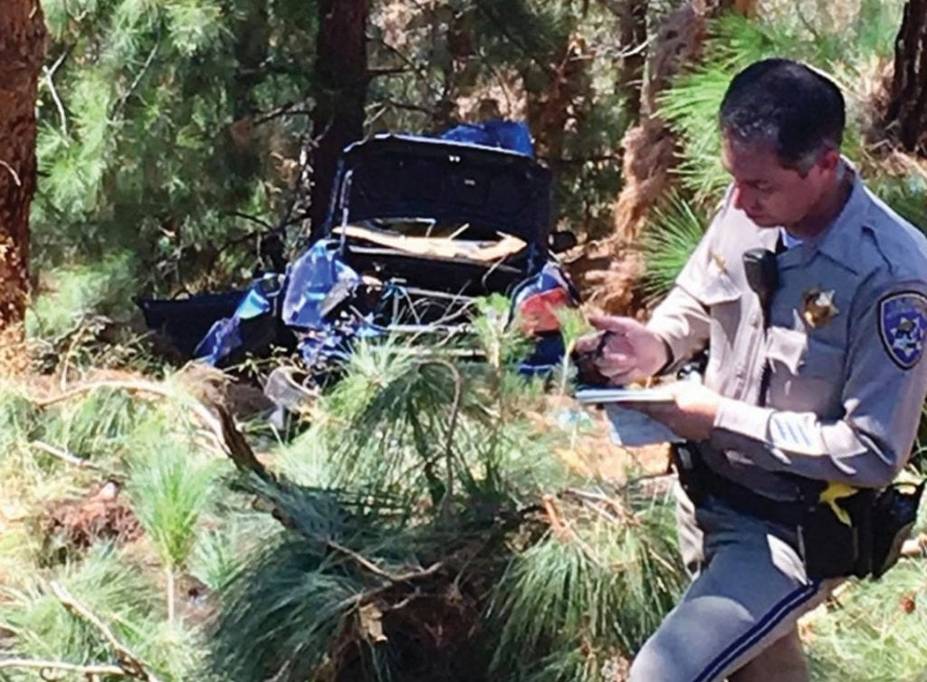 FATALITY—As the wrecked car is hauled out of the canyon next to Kanan Road, a deputy prepares his report. Courtesy of Malibu Search and Rescue