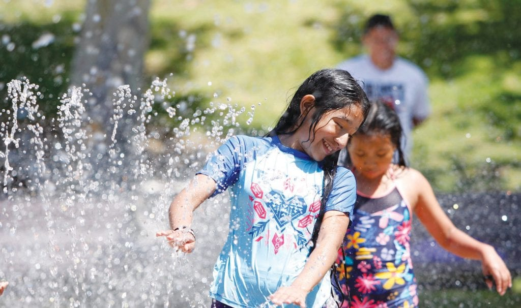 DRIP, DRY—Residents Astrid Escot, 12, (left) and Angie Escot, 10, enjoy the splash pad at Oak Canyon Community Park on Labor Day. The popular water play area in Oak Park remains open from 10 a.m. to 7 p.m. through Sept. 30. Photos by WENDY PIERRO/Acorn Newspapers