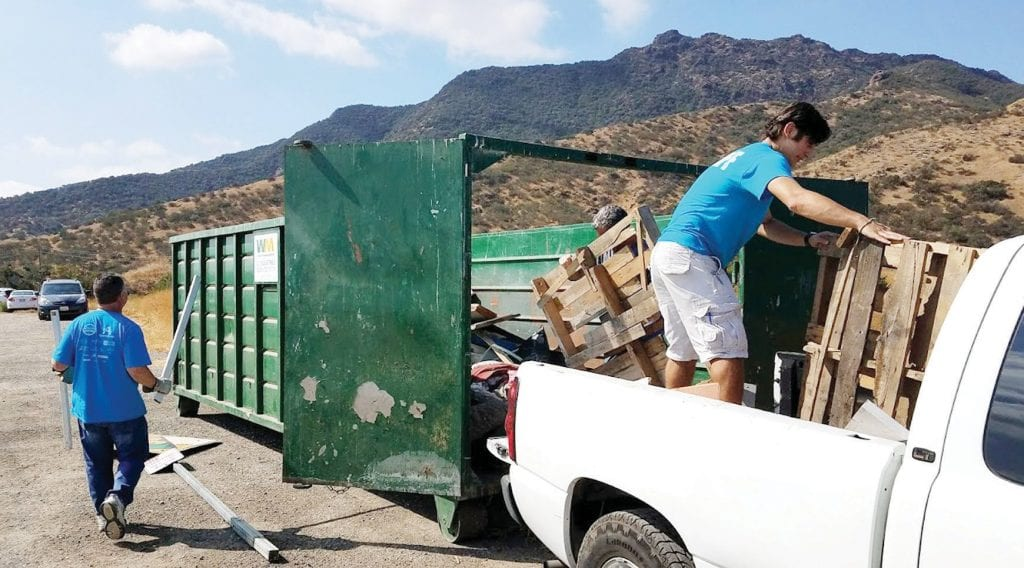 HAULING TRASH—Volunteers load a truck with trash during a previous creek cleanup. Below, Jeremy Wolfe and Morgan Culbertson assist with an earlier Heal the Bay event. Courtesy of Jeremy Wolf