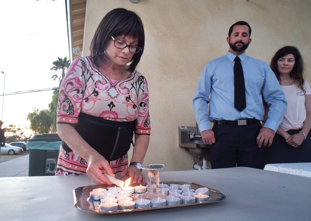 LET THERE BE LIGHT—Thousand Oaks resident Cathy Cole uses candles for Rosh Hashanah to illustrate the physical manifestation of spiritual light on Sept. 9 at Chabad of Thousand Oaks' new location. Cole is a founding member of the T.O. Chabad. JOSEPH A. GARCIA/Acorn Newspapers