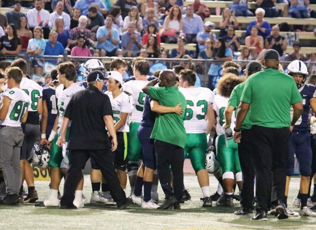 GOODWILL—Thousand Oaks High football players and coaches embrace Saugus players before their Sept. 7 game at College of the Canyons. Saugus junior Christian Nsubuga died days before the game. Courtesy of Paulette Worthy