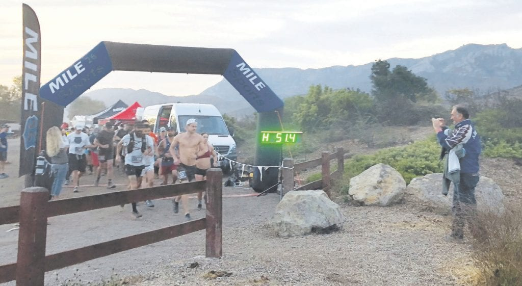 KEEP ON GOING—Hiawatha Trail Race runners at a mile-marker during an Oct. 6 event. SoCal Ultra Running, which hosts trail running events in the Santa Monica Mountains and beyond, sponsored eight runners from Back On My Feet, a nationwide program that helps persons conquer homelessness through the discipline of a long-distance running program. DAWN MEGLI-THUNA/Acorn Newspapers