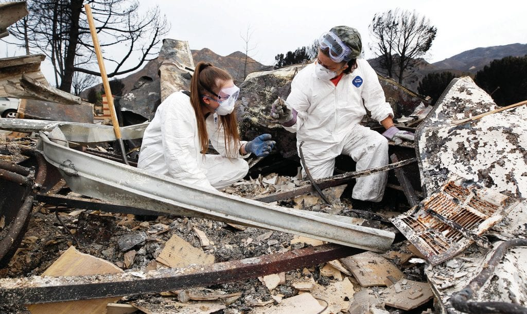 SEARCHING—Seminole Springs Mobile Home Park resident Tammy Odell shows her daughter Kelly a piece from one of her dolls that she found while sifting through the ashes of their home on Nov. 19. Theirs, like many others, was a complete loss. RICHARD GILLARD/Acorn Newspapers