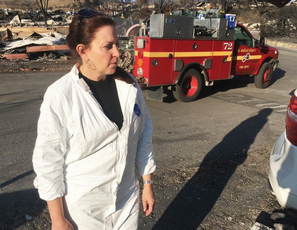 """FUTURE IS UNCERTAIN—Jena Weiss stands near the remains of her home, one of the more than 100 that were destroyed in Seminole Springs park by the Woolsey fire. """"I feel kind of abandoned,"""" she said. IAN BRADLEY/Acorn Newspapers"""