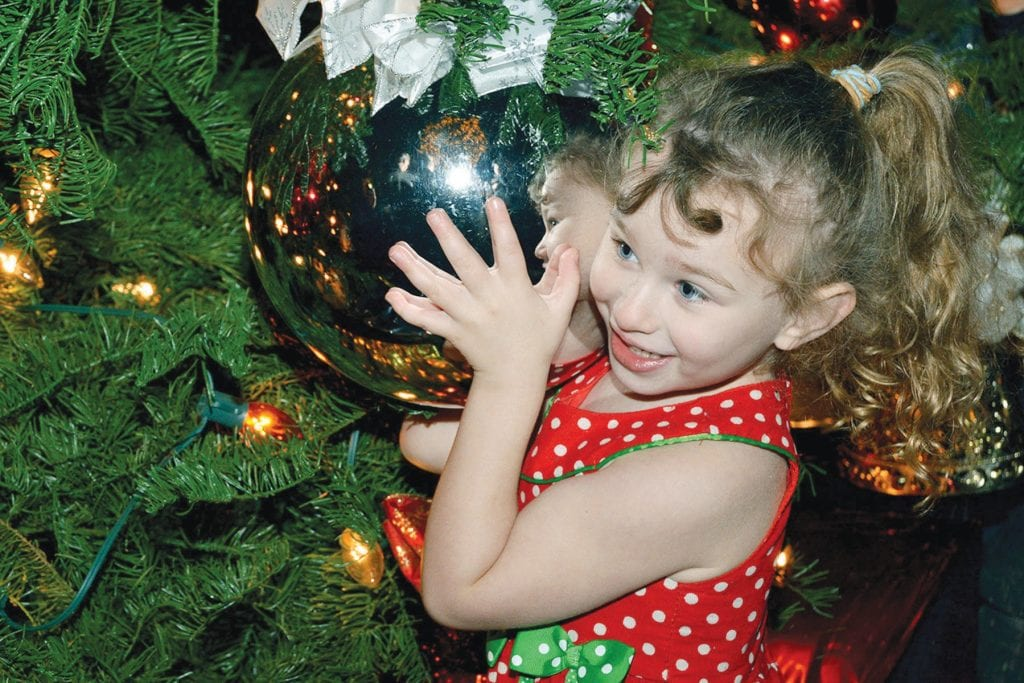 SHINY AND BRIGHT—Agoura Hills resident Ashlyn Kimmel, 3, clutches a Christmas tree ornament during the Promenade at Westlake's annual holiday program and tree lighting on Nov. 30. The event also included live music, acrobats, magicians, jugglers, strolling carolers, falling snow, a choir, face painting and food samples.