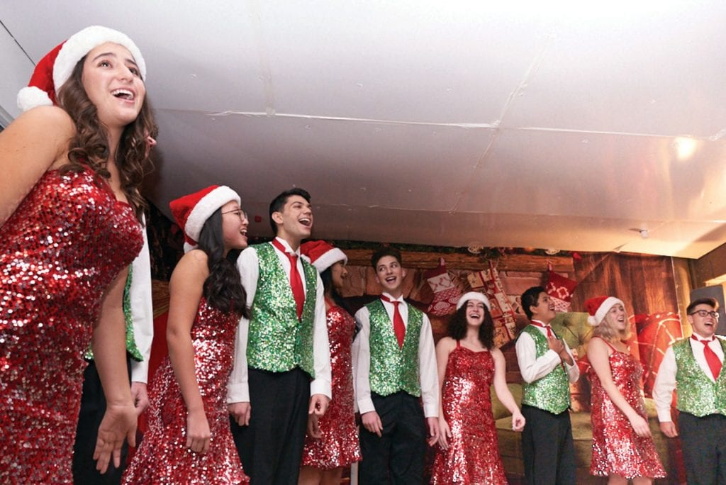 HOLIDAY SPARKLE—Above, A Class Act from Westlake High School entertains guests at the Westlake Yacht Club's annual Boat Parade of Lights event on Dec. 2. From left are Isabel Galvin, Garrett Cypher, Julia Zhong, Joseph Sipos, Anagha Iyer, Josh Karasik, Alexandra Karasik, Matt Guevara, Taylor Jones and Vince Baurio. Right, the Holiday Belle, owned by Philip and Donna Landry of Westlake Village, wins the Most Creative Design award.