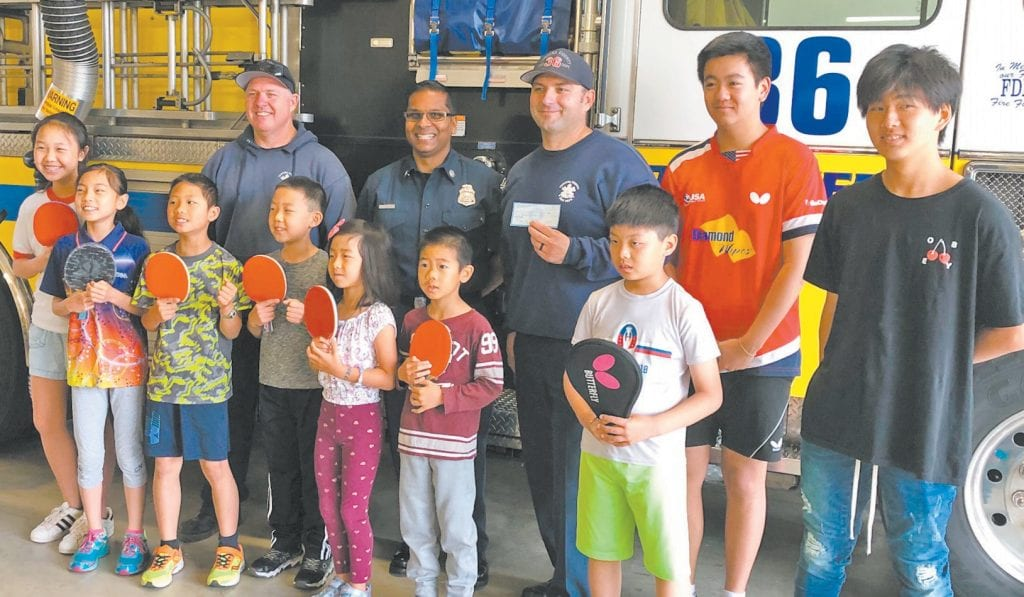 SERVE THE COMMUNITY—Jonathan Qin, second from right, and his table tennis academy students present a check to members of Oak Park Fire Station No. 36 in appreciation for their efforts fighting the Woolsey fire. Courtesy photo