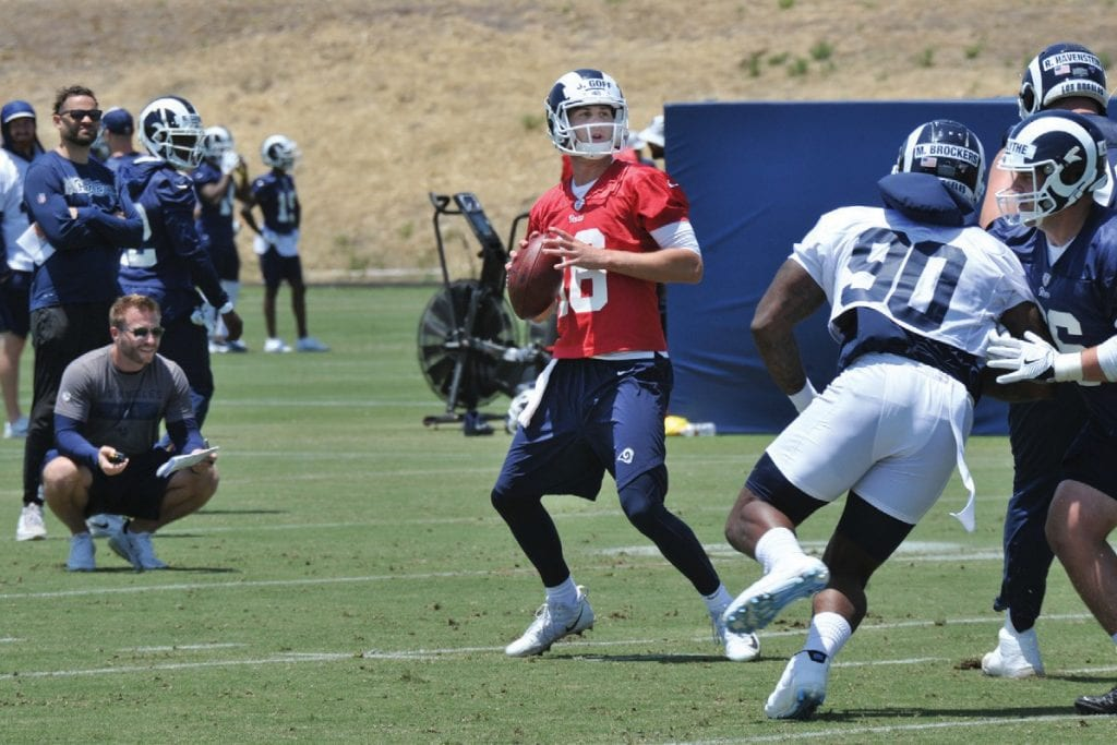 BACK TO WORK—Rams head coach Sean McVay, crouching at left, watches QB Jared Goff during organized team activities on June 3.