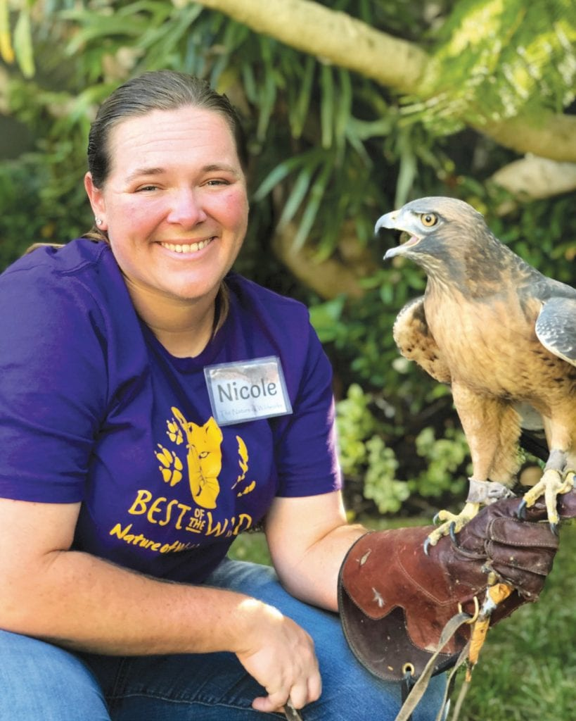 CAREGIVERS—Above, Nicole Wilson holds a red-tailed hawk at the 25th anniversary event. At right, president of Wildworks and the homeowner where the event took place and Mollie Hogan, founder and animal trainer.