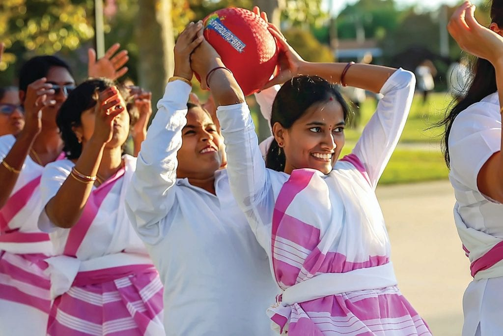HAND-ON FUN—Hundreds of Hindus from across the region spent Oct. 19 at Borchard Community Park in Newbury Park to celebrate Vijayadasami (vee-ja-ya-da-sha-mi), one of the most important holidays on the Hindu calendar. At top, Asha Appajigowda of Burbank passes a ball backward during a group competition. At right, Sampriti Thakur leads a traditional Saraswati dance. Below, the Thousand Oaks chapter marches in rhythm.
