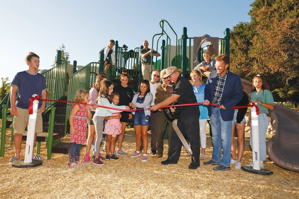 NEW VIEW— Above, Rancho Simi Recreation and Park District Board of Director member Mark Johnson helps children cut the ribbon Oct. 3 to reopen the playground at Eagle View Park. The equipment was destroyed during the Woolsey fire. At right, a new bridge and picnic tables replaced ones burned in the fire.