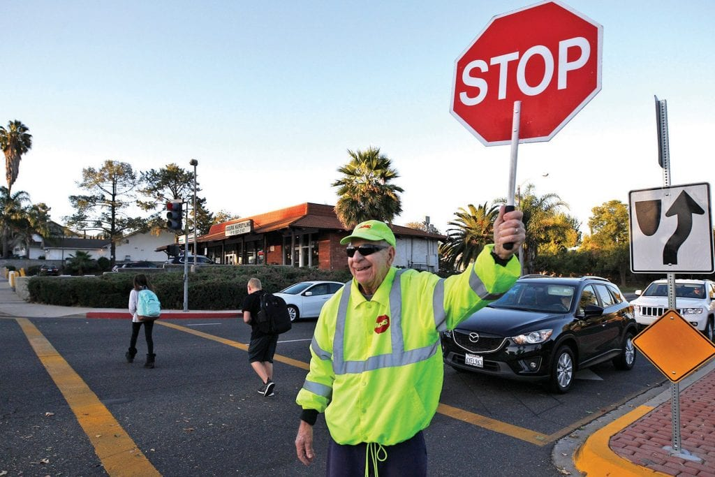 BIG BABY—Jerry Cadish keeps guard at the Lake Lindero crosswalk. Left, with an adoring member of the family. He is SoCal's oldest crossing guard. RICHARD GILLARD/Acorn Newspapers