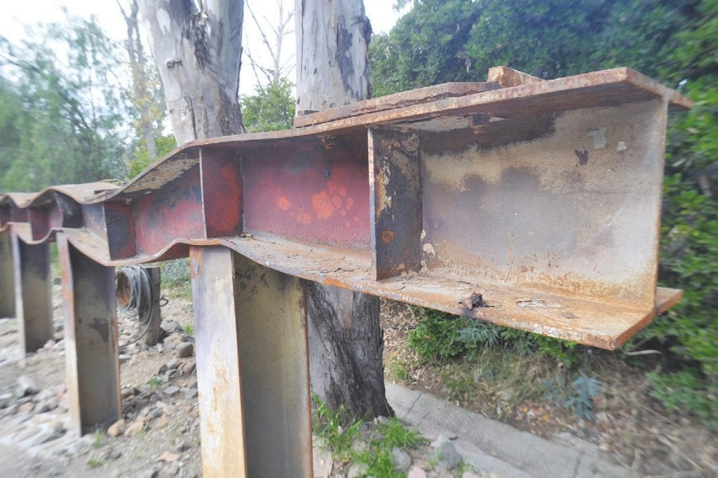 ACROSS TROUBLED WATERS—Right, officials break ground Jan. 11 on the $7-million bridge near Mulholland Highway and Troutdale Drive. A temporary structure is behind them. The previous bridge burned in the 2018 Woolsey fire and a remnant piece of steel, shown above, stands at the nearby Old Place restaurant in Cornell as a reminder of the tragedy.